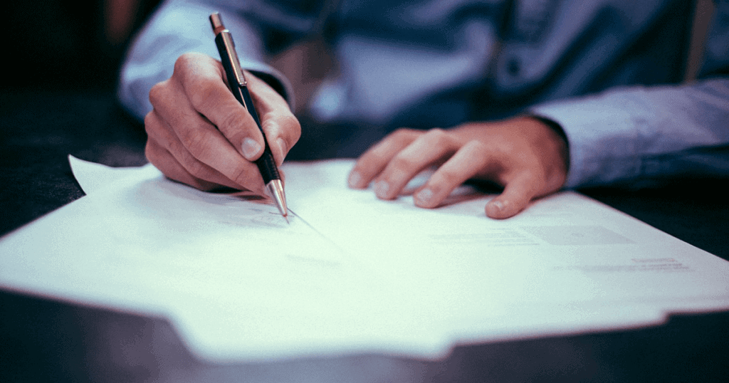 A business person writing notes on paper with a pen. Writing a press release like the one pictured doesn't have to be tough or mind-bending —learn more.