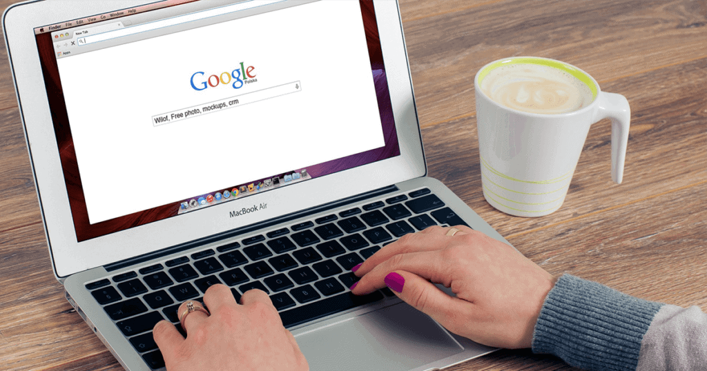 A woman typing on an apple laptop, typing search queries about CRMs and other digital marketing buzzwords into a Google search bar. A cup of coffee is on the wooden table next to the laptop. Modern SEO best practices center around the user, like the woman pictured here. Learn more.