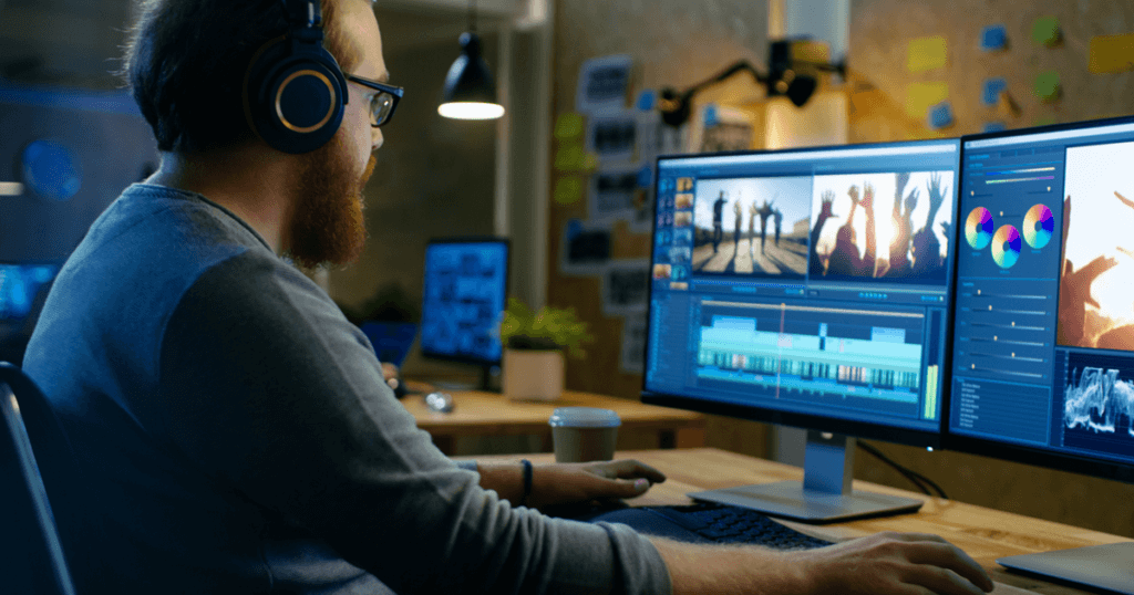 A man with a beard and glasses sits at a dual-monitor workstation, editing videos. IGTV, a popular video app, is an effective marketing tool. Tips are provided in this post.