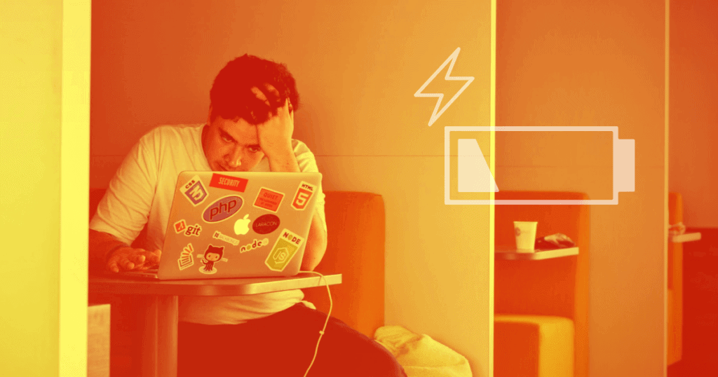 A man in a white T-shirt sits in front of a laptop computer covered in stickers. He has his head resting on his left hand, looking exhausted. There is an icon representing a low battery level to the right. Burnout is a serious problem for business owners.