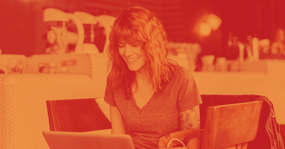 Pictured is a smiling woman working at a laptop computer at table surrounded by four chairs. She is in a cafe, working on content and branding for her business.