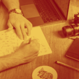 A man writes on a notebook trying to find the perfect font for his brand style guide. This is one of the many aspects of a brand style guide and is a crucial component of a marketing plan.