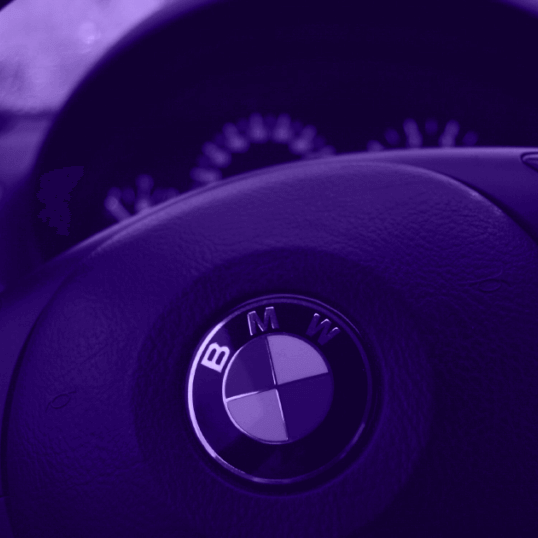 A modern dashboard and car steering wheel baring the BMW logo is pictured, shaded in purple. BMW is a great example of why branding beats marketing.