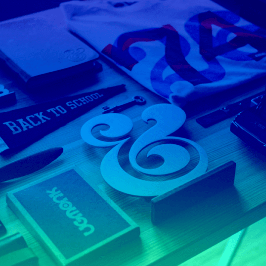 Becoming Branding Beasts—a number of items, including a pennant, a folded T-shirt, and a book, are laid out on a wooden table. The photo has a dark blue to aqua gradient.