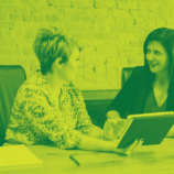 Two women are sitting at a table in front of a laptop computer, discussing a customer IEP. The photo appears in green and black.