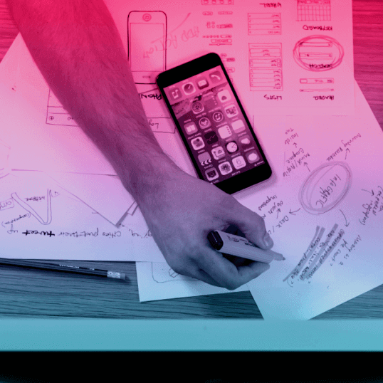 "An overhead view of a person's desk. Their hands are visible, holding a highlighter. Next to a number of documents is a cell phone. The person may be working on an answer to the question, ""What is digital marketing?"""