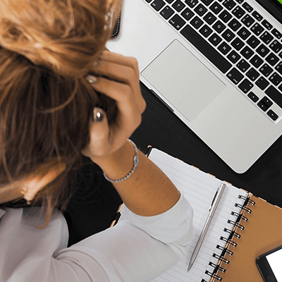 A woman hunched over her computer with her head in her hand. If you're spending a lot of time on your content marketing and it's still failing, here's what you might be doing wrong.